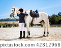 Appealing dark-haired woman standing near white saddle horse 42812968