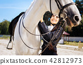 Dark-haired female rider with long braid taking care of her horse 42812973
