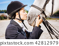 Loving horsewoman with red nail art kissing her white horse 42812979