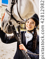 Dark-eyed smiling female rider coming to race track on her day off 42812982