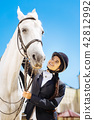 Dark-haired rider with long braid preparing for horse riding 42812992