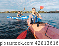 Blue-eyed woman feeling excited while rowing for the first time 42813616