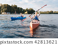Beaming woman wearing life vest holding paddles while kayaking 42813621