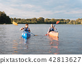 Blonde-haired man looking at his lovely girlfriend while kayaking 42813627