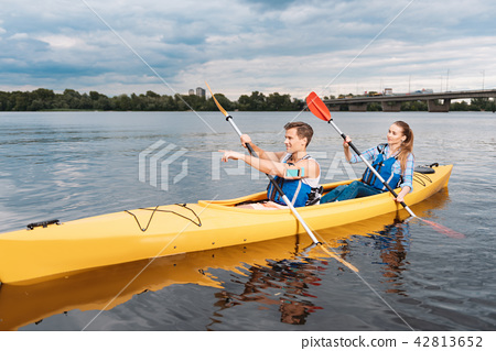 Blonde-haired man kayaking with his girlfriend showing her the way 42813652