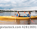 Modern couple holding paddles while kayaking on weekend 42813691
