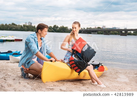 Caring blonde-haired husband telling his woman about kayaking 42813989