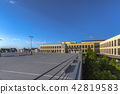 Empty parking lot with trees and office building 42819583