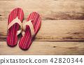 Red slipper on wooden 42820344