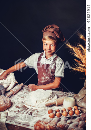 cute little boy with chef hat cooking 42822913
