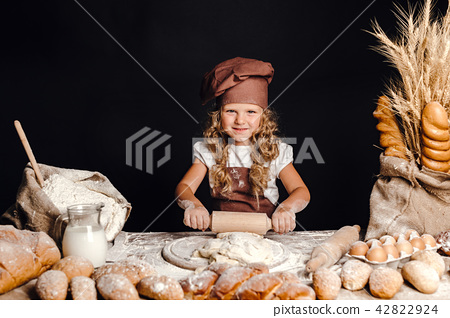 Little girl kneading dough at table 42822924