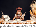 Little girl kneading dough at table 42822976