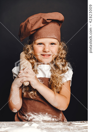 Little girl kneading dough at table 42823009