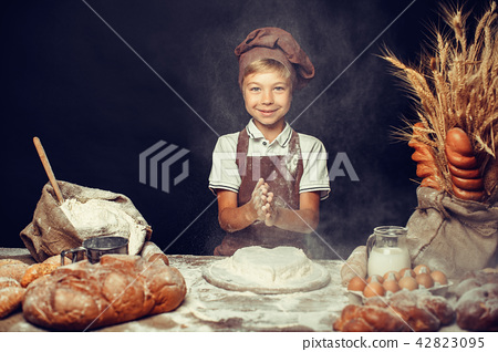 cute little boy with chef hat cooking 42823095
