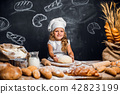 Little girl kneading dough at table 42823199