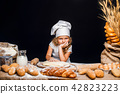 Little girl kneading dough at table 42823223