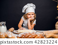 Little girl kneading dough at table 42823224