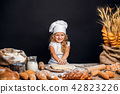 Little girl kneading dough at table 42823226