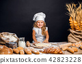 Little girl kneading dough at table 42823228