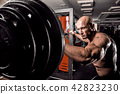 Bald Bodybuilder preparing for exercise with barbell in gym 42823230