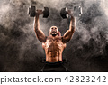 Bald Topless Muscular Man Doing Exercises With Two Dumbbells On Bench Press In Smoke 42823242