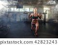 Young sexy girl in the gym doing squat on smoke background 42823243