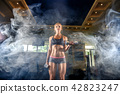 Sexy athlete blonde fitness woman in the gym workout with dumb on bicep. smoke 42823247