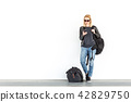 Fashionable young woman using her mobile phone while standing and waiting against plain white wall 42829750