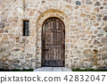 wooden door and very small window on stone house 42832047