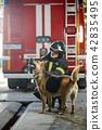 Photo of fireman squatting next to shepherd near fire engine 42835495