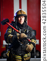 Photo of fireman with sledgehammer in hands near fire engine 42835504