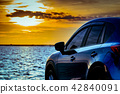 Blue compact SUV car parked near the sea at sunset 42840091