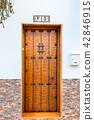 single wooden door with number thirteen on a wall 42846915
