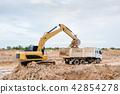 Yellow excavator machine loading soil into a dump  42854278