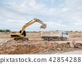 Yellow excavator machine loading soil into a dump  42854288