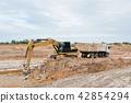 Yellow excavator machine loading soil into a dump  42854294