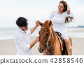 Young couple goes horse riding on tropical beach. 42858546