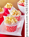 A red paper cup with popcorn. 42867640