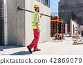Blue-collar worker carrying a heavy metallic bar during work 42869079