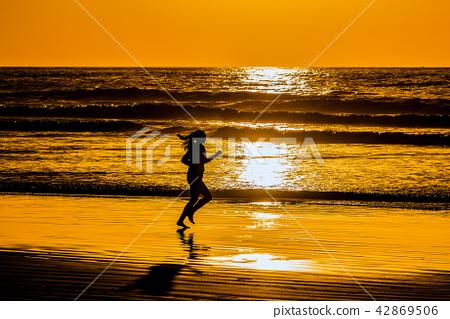 在黃昏·運行海灘的婦女的剪影 42869506