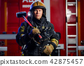 Photo of young fireman with sledgehammer in hands near fire engine 42875457