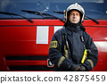 Photo of young fireman in front of red car 42875459