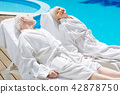 Retired man and woman wearing white bathrobes chilling near pool 42878750