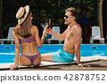 Slim woman wearing purple swimming suit sitting near boyfriend 42878752