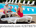 Slim retired woman wearing red swimming suit playing cards 42878879