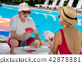 Funny happy pensioners entertaining sitting near big pool 42878881