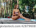 Slim model wearing swimming suit getting suntan in countryside 42879608