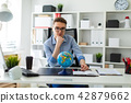 A young man sits in the office at a computer desk and in front of him stands a globe. 42879662