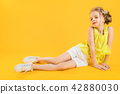 A teenage girl is sitting on a yellow background. 42880030