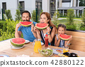 Happy positive family eating watermelons 42880122